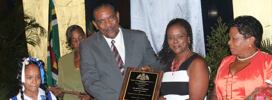 Principal of the year Gretta Roberts being presented with plaque by His Excellency Charles Savarin